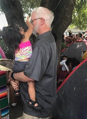 Pastors at Border Holding Child